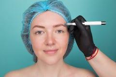 Permanente Make-up voor Wenkbrauwen Microblading brow Schoonheidsspecialist die wenkbrauw doen die voor vrouwelijk gezicht tatoe? stock foto