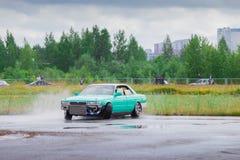 PERMANENTE, RÚSSIA - 22 DE JULHO DE 2017: Carro verde de derivação no asfalto molhado Foto de Stock