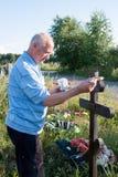 Permanente, Rússia - 13 de julho 2016: O homem pinta uma cruz de madeira Foto de Stock