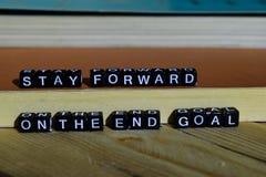Permanezca delantero en el objetivo final en bloques de madera Concepto de la motivación y de la inspiración imágenes de archivo libres de regalías