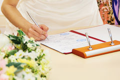 Permis ou contrat de mariage de signature de jeune mariée Images libres de droits
