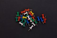 Perni colorati di spinta su un fondo nero Immagini Stock Libere da Diritti