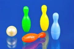 Perni di bowling dei bambini, variopinti su un fondo blu Il bowling è un gioco di sport delle palle e dei perni di bowling Lo sco fotografia stock