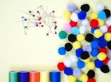 Perni, fili del cotone e mini pom-poms, accessori di cucito nel colore vivo fotografie stock libere da diritti