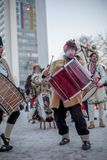 Kuker is loudly drumming to scary the evil away. PERNIK, BULGARIA - JANUARY 27, 2017: Male drummer with beard in traditional kuker fur costume with brown hat is Stock Photography