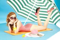 Perno atractivo hermoso de la muchacha para arriba en una reclinación brillante del bikini. Foto de archivo