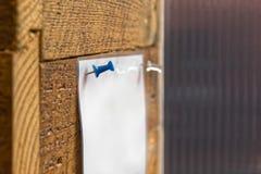 Perno azul del tablón de anuncios que soporta el aviso laminado en la pared de madera rústica del final imagen de archivo