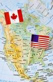 Perno de la bandera de Canadá y de los E.E.U.U. en mapa Fotografía de archivo libre de regalías