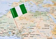 Perno de la bandera de Nigeria en mapa Imágenes de archivo libres de regalías