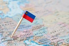 Perno de la bandera de Liechtenstein en un mapa del mundo imagen de archivo