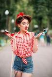 Perno del encanto encima de la muchacha con los teléfonos rotatorios retros Fotografía de archivo libre de regalías