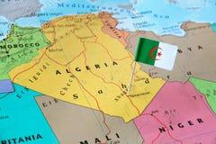 Perno della bandiera dell'Algeria sulla mappa immagini stock libere da diritti