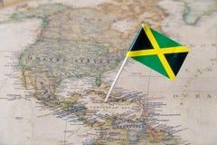 Perno della bandiera della Giamaica sulla mappa di mondo Fotografia Stock