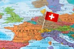 Perno della bandiera della Svizzera sulla mappa Fotografia Stock