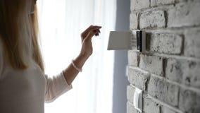 Perno entrante della donna sulla tastiera dell'allarme di sicurezza domestica stock footage
