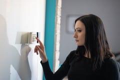 Perno entrante di sicurezza della donna castana sulla tastiera domestica dell'allarme fotografia stock libera da diritti