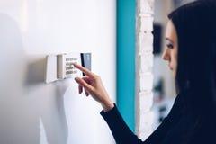 Perno entrante di sicurezza della donna castana sulla tastiera domestica dell'allarme immagini stock libere da diritti
