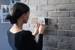 Perno entrante di sicurezza della giovane donna sulla tastiera domestica dell'allarme fotografia stock libera da diritti
