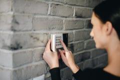 Perno entrante di sicurezza della giovane donna sulla tastiera domestica dell'allarme immagine stock
