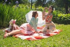 Perno grazioso due sulle signore che hanno picnic piacevole nel parco della città in un giorno soleggiato insieme gli amici di ra immagini stock