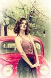 Perno grazioso sulla ragazza che posa su un retro fondo rosso dell'automobile Sguardo fisso allegro riparato sulla macchina fotog fotografia stock