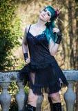 Perno hermoso joven encima de la muchacha del encanto con el pelo del color verde, altas botas en balcón de piedra viejo del vint Foto de archivo