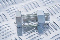Perno inoxidable y nuez roscada en la construcción plateada de metal acanalada Foto de archivo