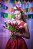 Perno joven hermoso del vintage encima de la muchacha del estilo que se coloca en la escena encendida colorida que sostiene las f Fotografía de archivo