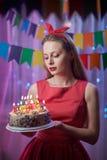 Perno joven hermoso del vintage encima de la muchacha del estilo que se coloca en torta encendida colorida de la tenencia de la e Foto de archivo libre de regalías