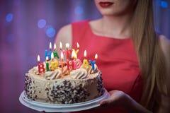 Perno joven hermoso del vintage encima de la muchacha del estilo que se coloca en torta encendida colorida de la tenencia de la e Imagen de archivo