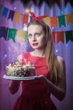 Perno joven hermoso del vintage encima de la muchacha del estilo que se coloca en torta encendida colorida de la tenencia de la e Fotos de archivo