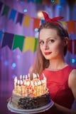 Perno joven hermoso del vintage encima de la muchacha del estilo que se coloca en torta encendida colorida de la tenencia de la e Imágenes de archivo libres de regalías