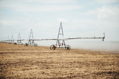 Perno mobile di irrigazione che innaffia un campo Fotografia Stock Libera da Diritti