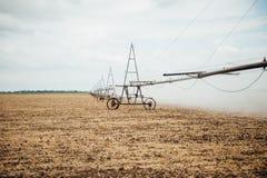 Perno mobile di irrigazione che innaffia un campo Immagini Stock
