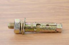 Pernos de ancla de la manga en una superficie de madera del banco de trabajo imágenes de archivo libres de regalías