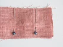 Pernos de costura en la tela de lino en el fondo blanco, uso de costura del perno para atar la tela junta temporalmente antes de  foto de archivo