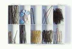 Pernos de pelo de la fijación en una caja plástica en blanco Fotografía de archivo