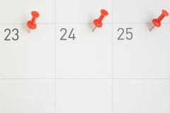 Pernos rojos fijados las fechas del mes en el papel del calendario Fotos de archivo