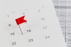 Pernos rojos a los gatos monteses en el calendario al lado del número de fiftee fotos de archivo