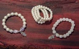 Perolize a joia feita sob encomenda do bracelete na madeira ou no fundo de pedra imagem de stock