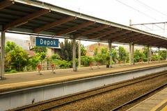 Peron e estrada de ferro na estação de Depok com o céu branco como o fundo e árvores perto da estação Depok recolhido foto Fotografia de Stock Royalty Free
