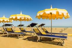 Зонтики и sunbeds - пляж Римини, Италия Стоковое Изображение