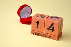 A perpetual calendar with February 14 and a red velvet gift box with a gold diamond ring. Concept of love and Valentines Day royalty free stock image
