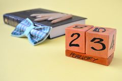 Perpetual wooden calendar with date of February 23, a bow tie, a book and pencils on a yellow background with copy space. Concept of Defender of the Fatherland royalty free stock photos