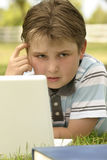 Perplexed. A puzzled looking boy working on the computer outdoors Royalty Free Stock Image