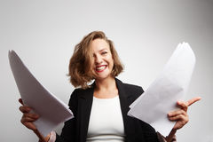 Perplexed accountant doing financial reports holding documents in her hands. Royalty Free Stock Images