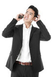 Perplexed businessman answering phone call Royalty Free Stock Images
