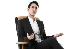 Perplexed businessman on a chair Royalty Free Stock Image