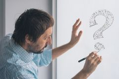 Perplexed businessman drawing question marks on whiteboard. In the office, selective focus stock photo
