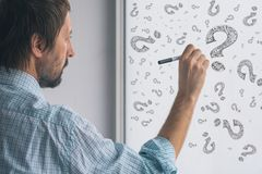 Perplexed businessman drawing question marks on whiteboard. In the office, selective focus royalty free stock photos